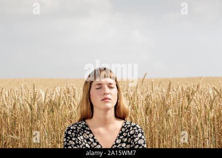 Porträt der jungen Frau mit geschlossenen Augen entspannen in Vorderseite des Korntanks Feld