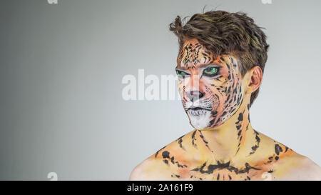 Portrait von ein Kerl wie ein Tiger auf einem grauen Hintergrund gemalt. Gesicht Färbung - Stockfoto