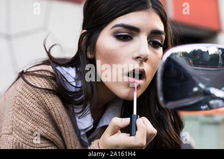 Porträt der jungen Frau Anwendung Lippenstift draußen