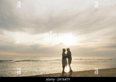 Silhouette von Senior Paar ständigen Gesicht am Strand zu Gesicht von Sonnenuntergang, Liepaja, Lettland Stockfoto