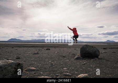Junge Frau einen Sprung von einem Felsen im vulkanischen Hochland von Island - Stockfoto