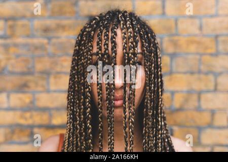 Porträt der jungen Frau mit langen Zöpfen, die ihr Gesicht