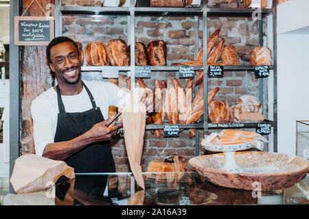 Lächelnd Mann in einer Bäckerei arbeiten - Stockfoto