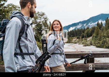 Junges Paar auf einer Wanderung zu Fuß auf Holzbrücke, Vorderriss, Bayern, Deutschland - Stockfoto