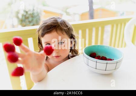 Süße kleine Mädchen mit Himbeeren auf Ihre Fingerspitzen - Stockfoto