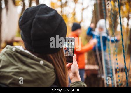 Glückliche junge Familie mit Kleinkind Kind Sohn Spielen am Spielplatz Mutter unter Bild auf dem Telefon