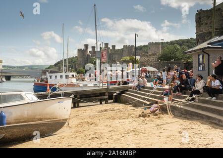 Touristen genießen Sie einen warmen und sonnigen Sommer am Nachmittag am Kai im Schatten der historischen Burg und Stadt Conwy, [Conway] Gwynedd, Wales UK - Stockfoto