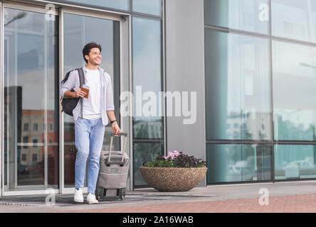 Glückliche Kerl aus dem Flughafengebäude mit Gepäck - Stockfoto