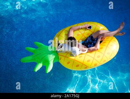 Teenager halten auf ein Mobiltelefon und seinem kleinen Hund entspannen an einem Sommertag, flott auf einer aufblasbaren Ananas in einen Außenpool. - Stockfoto