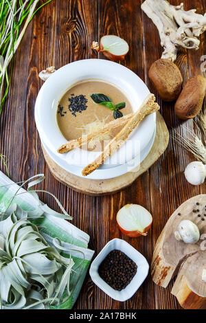 Pilz Suppe mit Nudeln mit Champignons und Kräutern auf braunem Holz- Hintergrund - Stockfoto