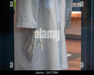 Moskau, Russland - 14. September 2019: Skeleton Hand und ein weißes Gewand hinter Glas in einem kiehls Store Fenster. Marke Einzelhändler, der in der Haut spezialisiert hat, ha - Stockfoto