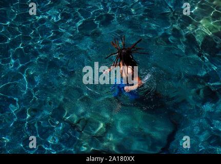 Junger Mann mit langen dreadlocks genießen, klaren, blauen Wasser Strand Stockfoto