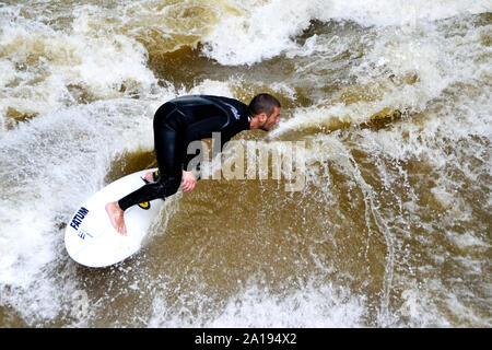 München/Deutschland - vom 13. Juli 2019: Surfer reitet der künstlichen Wellen am Eisbach, einem kleinen Fluss in München. - Stockfoto