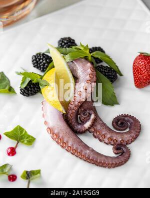Octopus mit Beeren auf der Platine - Stockfoto