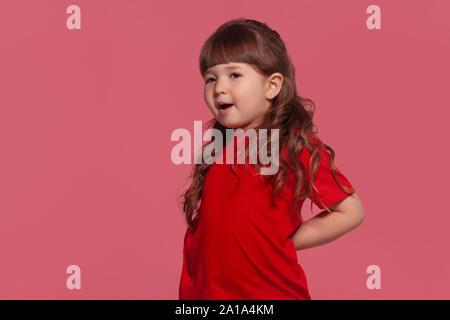 Nahaufnahme Porträt einer kleine dunkelhaarige Mädchen gekleidet in ein rotes T-Shirt gegen ein Pink Studio Hintergrund posiert. Aufrichtige Gefühle Konzept. - Stockfoto