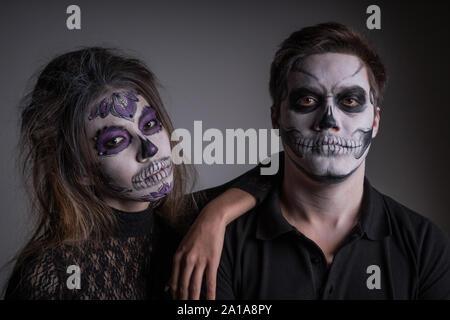 Ein Kerl und ein Mädchen mit gemalten scary Ghost Masken auf ihren Gesichtern zu Ehren von Halloween - Stockfoto