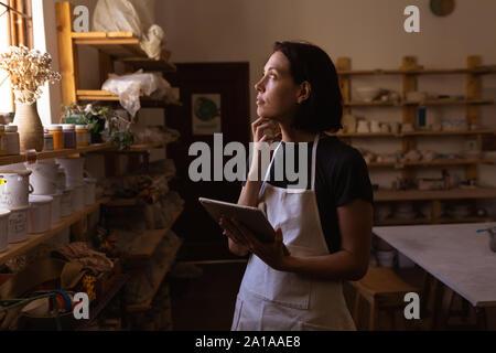 Weibliche Potter mit Tablette in einer Töpferwerkstatt