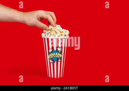 Ein Mann mit Popcorn aus einem Eimer auf rotem Hintergrund - Stockfoto