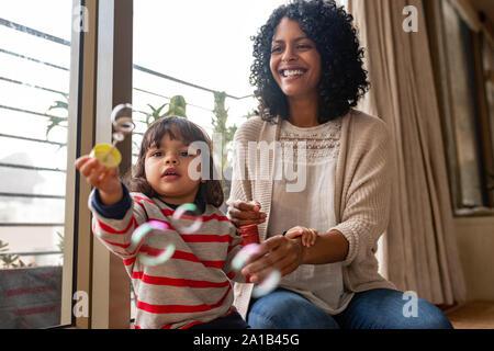 Kleine Mädchen und ihre Mutter spielt mit einer Blase Zauberstab