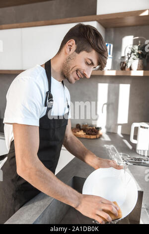 Attraktive junge Mann ist Geschirrspülen in seiner Küche - Stockfoto