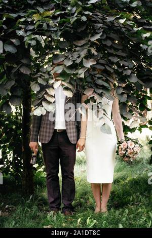 Hochzeit paar steht unter grünen Bäumen mit Flächen von Laub und halten die Hände versteckt - Stockfoto