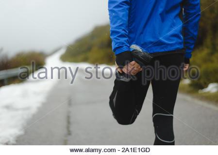 Detail der Athlet Aufwärmen und Stretching vor der Ausführung unter dem Schnee im Winter Mountain Road. - Stockfoto