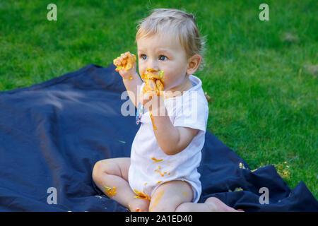 Ein adorable Baby Boy genießt seinen ersten Geburtstag feiern auf einer Party mit einem Kuchen smash eines bunten iced Kuchen draußen im Garten