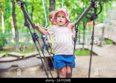 Portrait von niedlichen kleinen Jungen und Mädchen zu Fuß auf einer Hängebrücke in ein Abenteuer Hochseilgarten. - Stockfoto
