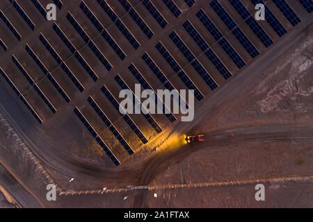 Holen Sie den LKW mit den Lichtern an und IT-Mitarbeiter den Tag fertig für nach Hause. Ein Blick auf einen abgelegenen Solarenergiepark mit Solarmodulen Stockfoto