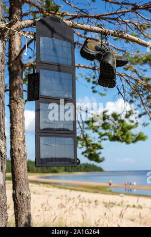 Tragbare solar panel auf einer Pinie, und lädt das Handy im Feld Bedingungen vor dem Hintergrund der Strand mit Leuten, Nea hängen - Stockfoto