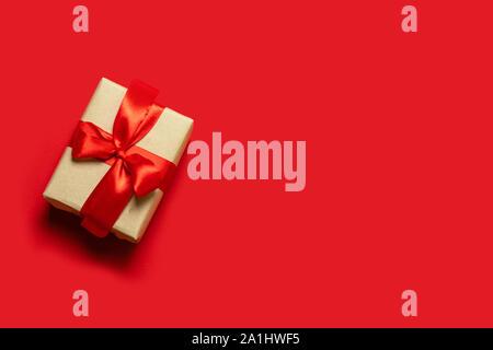Weihnachtsgeschenk. Kreative Banner mit handgefertigten craft Box und einer roten Schleife auf einem roten Hintergrund. - Stockfoto