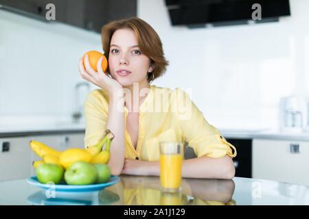 Wunderschöne Frau trinkt ein Glas Orangensaft stehen in ihrer Küche - Stockfoto