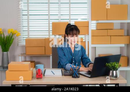 Bezaubernd schöne asiatische Teenager Eigentümer business Frau Arbeit zu Hause für Online Shopping, suchen die Reihenfolge, in der Laptop mit Büroausstattung, entreprene - Stockfoto