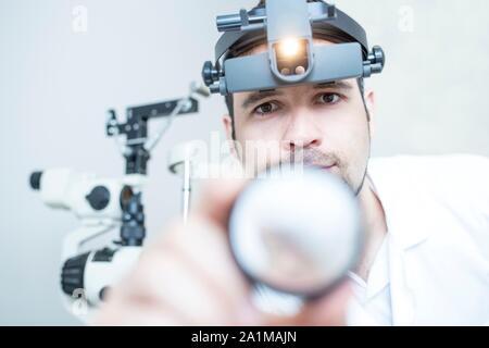 Indirekte ophthalmoskop Augenuntersuchung unterzogen werden. Augenarzt mit einem Head-mounted Ophthalmoskop. - Stockfoto