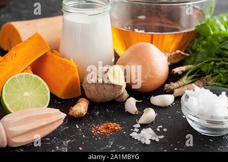 Kürbis, Kurkuma, Ingwer, Limetten, Kokos Butter, Kokosmilch, Zwiebel, Knoblauch, Kräuter auf Schwarz. Zutaten für Kürbis Kurkuma Suppe - Stockfoto
