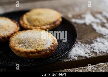 Drei Mince Pies auf einer schwarzen Platte auf einem rustikalen Holztisch mit Schnee - Stockfoto