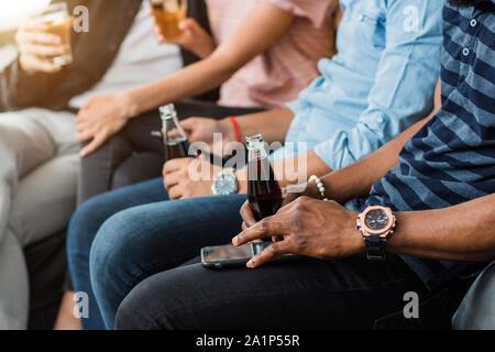 7/8 Schuß von jungen afrikanischen Mann, stilvolle Armbanduhr, hält in der Hand die Flasche mit Soft Drink und über Handy, sitzen auf den Sofa mit Fr