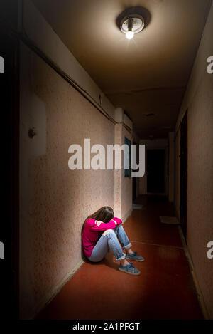 Eine traurige und verzweifelte Frau sitzt in einem dunklen Korridor durch ein düsteres Licht beleuchtet. Ihr Schmerz und ihre vielen Probleme drückte sie in die völlige Isolation. Hi - Stockfoto