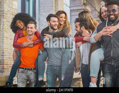 Vier multirassischen Paare Spaß unter der City Arkaden am Morgen huckepack. Studenten Spaß in der Stadt. - Stockfoto