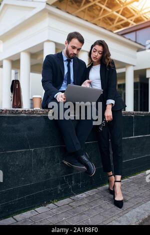 Junge Berufstätige diskutiert Deal in die Straße. in voller Länge Foto. - Stockfoto