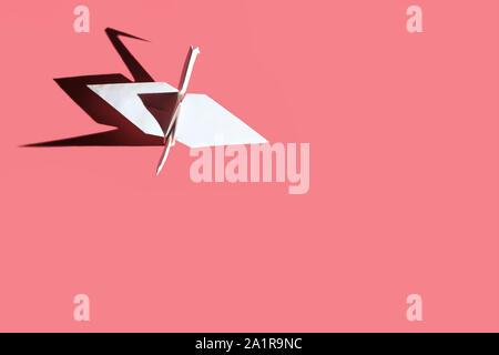 Origami Crane aus Papier auf einem hellen rosa Hintergrund mit einem harten Schatten - Stockfoto