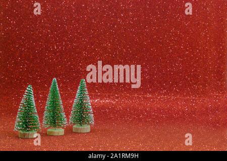 Drei Weihnachtsbäume aufgereiht auf einem roten Hintergrund. - Stockfoto