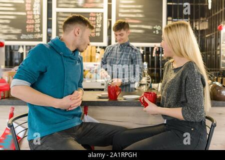 Junge lächelnde Mann und Frau gemeinsam im Gespräch im Café sitzen in der Nähe der Theke, ein paar Freunde trinken Tee, Kaffee - Stockfoto