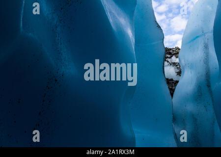 Sie suchen einen schmalen Eingang in eine Eishöhle mit dunklen blauen Wänden in der Matanuska Gletscher in Alaska.
