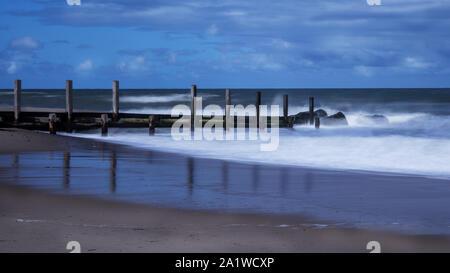 Buhnen im Meer bei Horsey Lücke in Norfolk fotografiert als lange Exposition, die Wellen zu glätten - Stockfoto