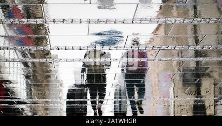 Unscharfe Reflexion Silhouette auf nasser Straße der Stadt von zwei touristischen Menschen zu Fuß unter dem Dach und Ziehen reisen Koffer im regnerischen Herbst Tag