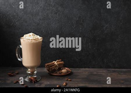 Irish Coffee mit Sahne, Gewürzen und Kaffeebohnen auf schwarzem Hintergrund Holz, kopieren. - Stockfoto