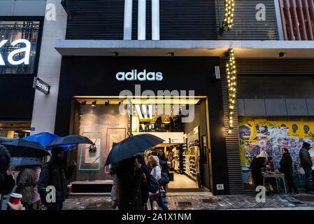 Athen, Griechenland - Januar 4, 2019: Anzeige eines Adidas shop Nachts mit Menschen um in Athen, Griechenland - Stockfoto