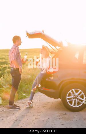Paar ruht auf dem Strand im Sommer in der Nähe des Flusses. Kaukasische Mann und Frau Bier trinken. - Stockfoto
