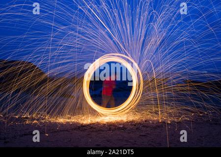 Ein Mann tun Circular spinning Licht Malerei mit Stahlwolle bei Nacht am Strand. - Stockfoto